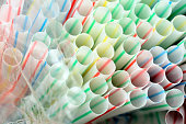 Colored plastic straws under plastic bag close up for plastic background