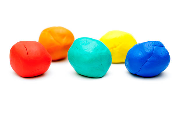 Colored plasticine on white background Five pieces of colored plasticine on white background. clay stock pictures, royalty-free photos & images