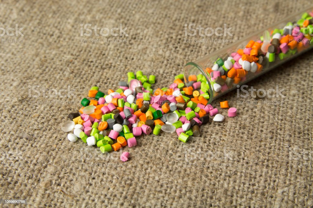 Colored Polyethylene granules on the background of the canvas from flax. BPA FREE stock photo