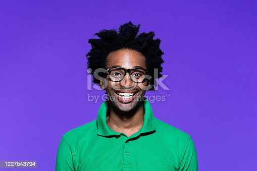 Portrait of surprised afro american young man wearing green polo shirt and nerdy glasses, laughing at camera. Studio shot on violet background.