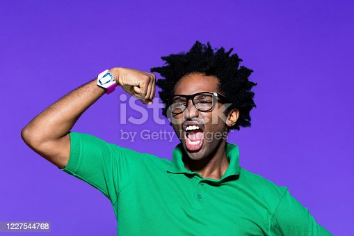 Portrait of confident afro american young man wearing green polo shirt and nerdy glasses, raising arms and flexing muscles. Studio shot on violet background.
