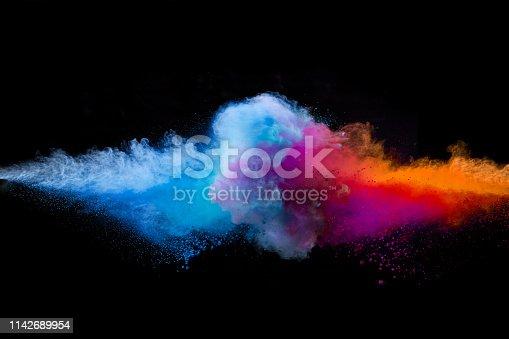 857348256istockphoto Colored powder explosion on black background. 1142689954