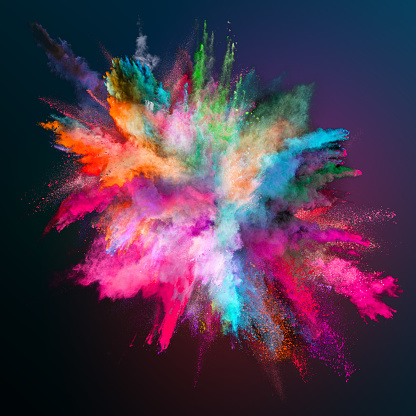 Colored powder explosion on dark gradient background.