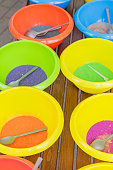 colored sand in plastic bowls. Workshop for making sand pictures for kids