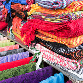 Colored shawls and scarves on the rack.