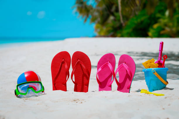 farbige hausschuhe, spielzeug und tauchen maske am strand - flitterwochen flip flops stock-fotos und bilder