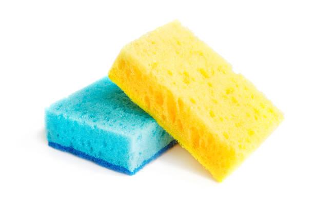 Farbige Schwämme zum Waschen von Geschirr und andere häusliche Bedürfnisse. Gelber Schwamm liegt auf blauem Schwamm in einem leichten Winkel. Isolieren – Foto