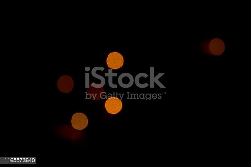 Colored spots of light on a black background. Black background with blurry red, yellow and orange stain. No focus.
