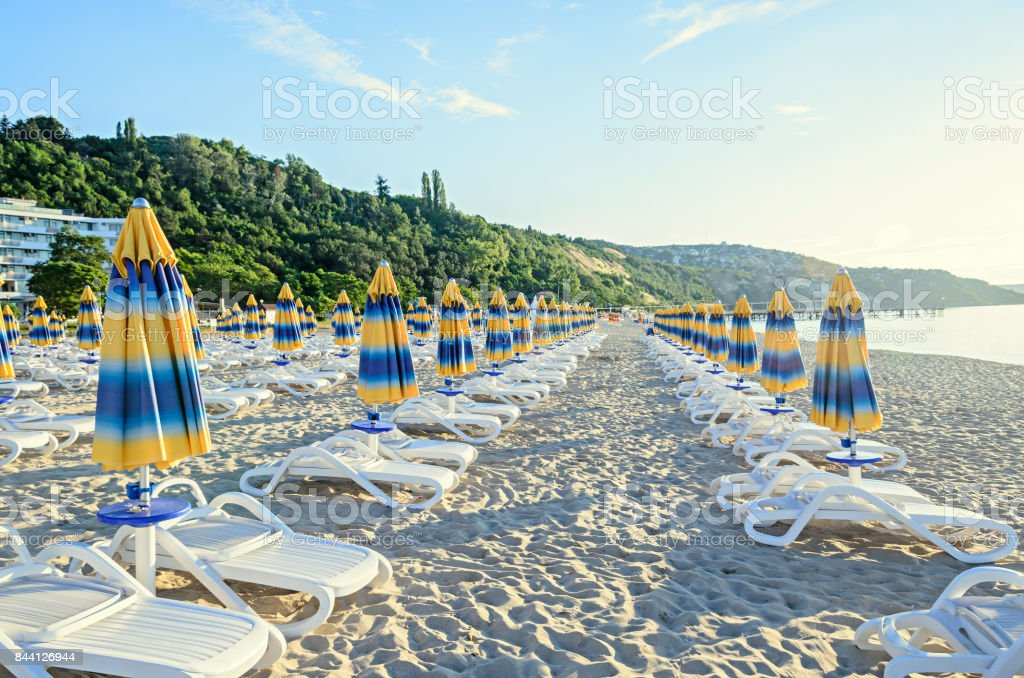 Colored stripped sun umbrellas, beach sand and beds stock photo