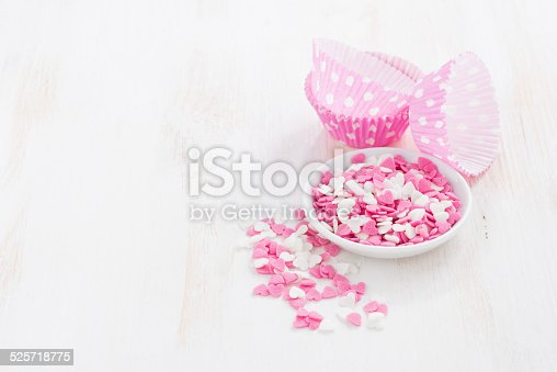 colored sugar hearts and paper baking dishes on white wooden table, horizontal