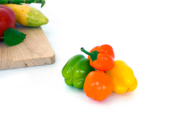 Colored sweet peppers on white with summer veggies stock photo