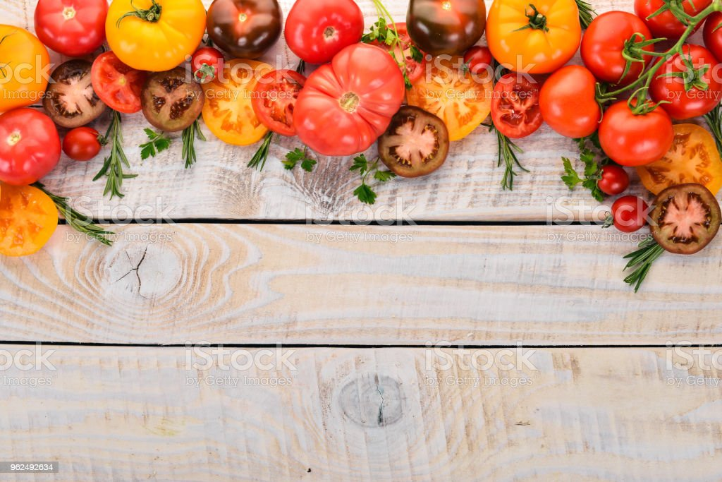 Colored tomatoes On a white wooden background. Top view. Copy space. - Royalty-free Cherry Stock Photo