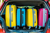 colored travel bags in car trunk