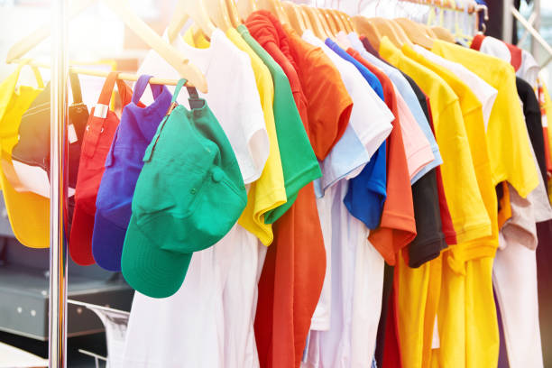 Colored t-shirts and caps in store stock photo