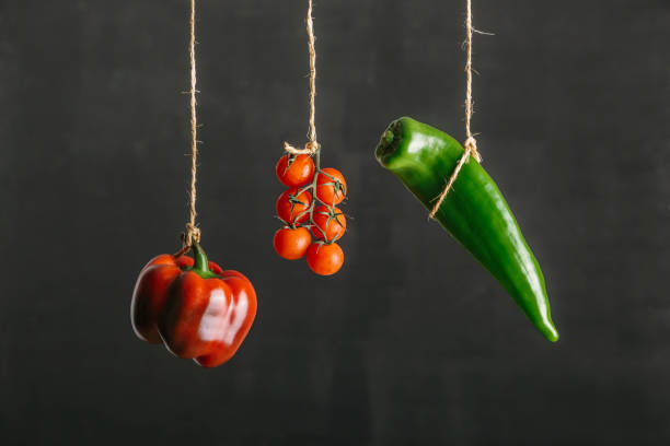 Colored vegetables, peppers and tomatoes, suspended on a string against black background stock photo