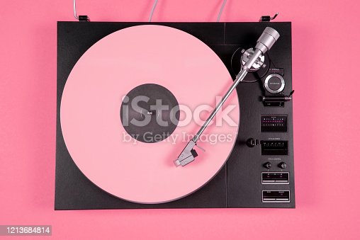 Colored vinyl record on a pink background with copy space. Top view.