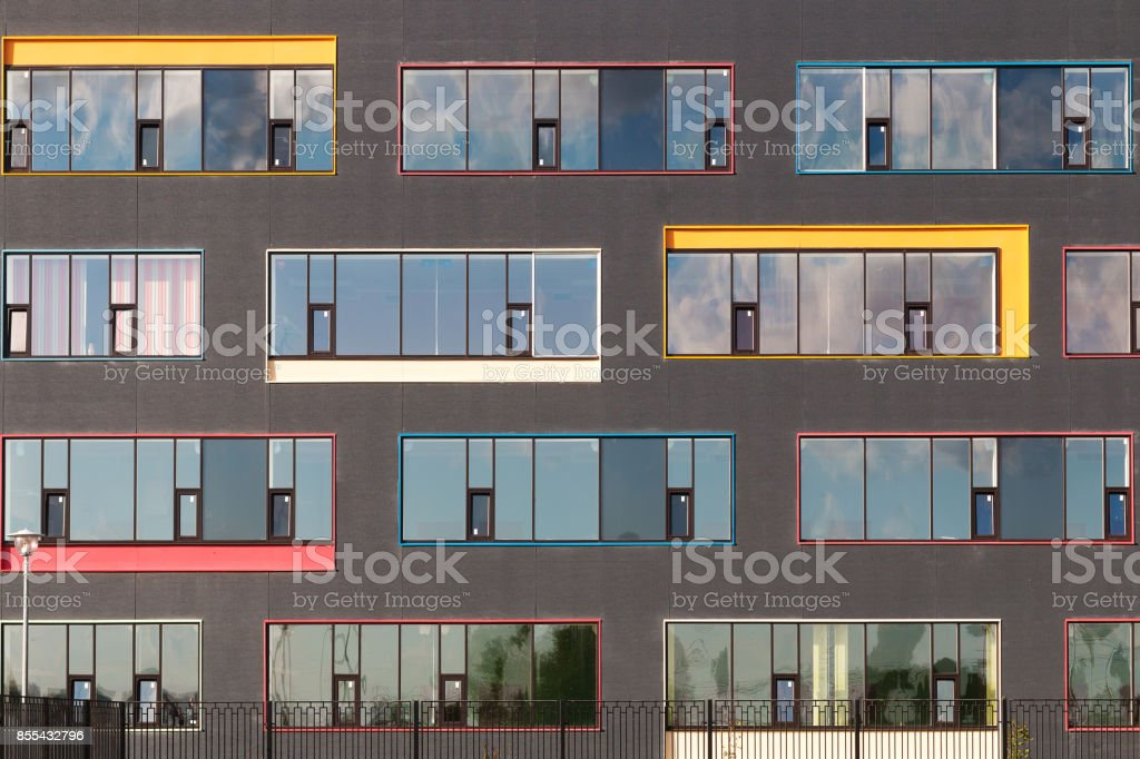Colored windows of the building with the sky reflected in the glass. Geometric background. Building's facade stock photo