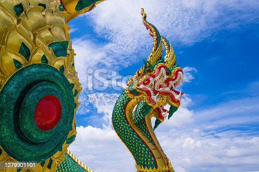 Low angle and side view of colorful 3-headed serpent statue against white cloud in blue sky background