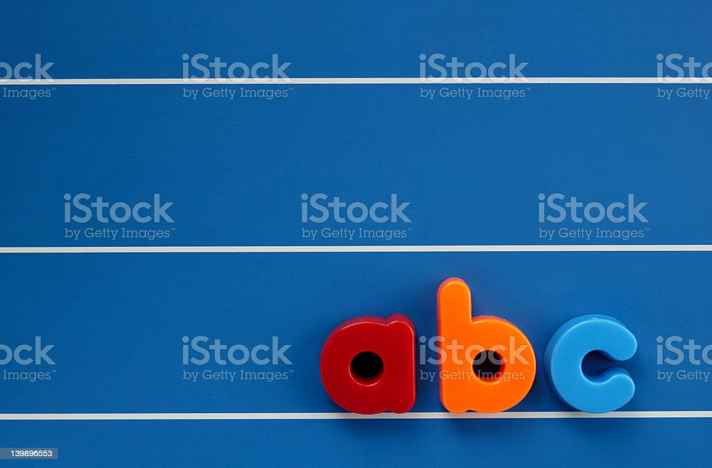 Colorful ABC children's magnet on a blue board stock photo