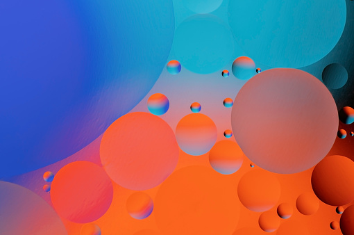 Colorful abstract background. Blue orange purple pink and red circles and oil bubbles in the water. Close up. Macro abstraction. Rainbow oil pattern and texture.