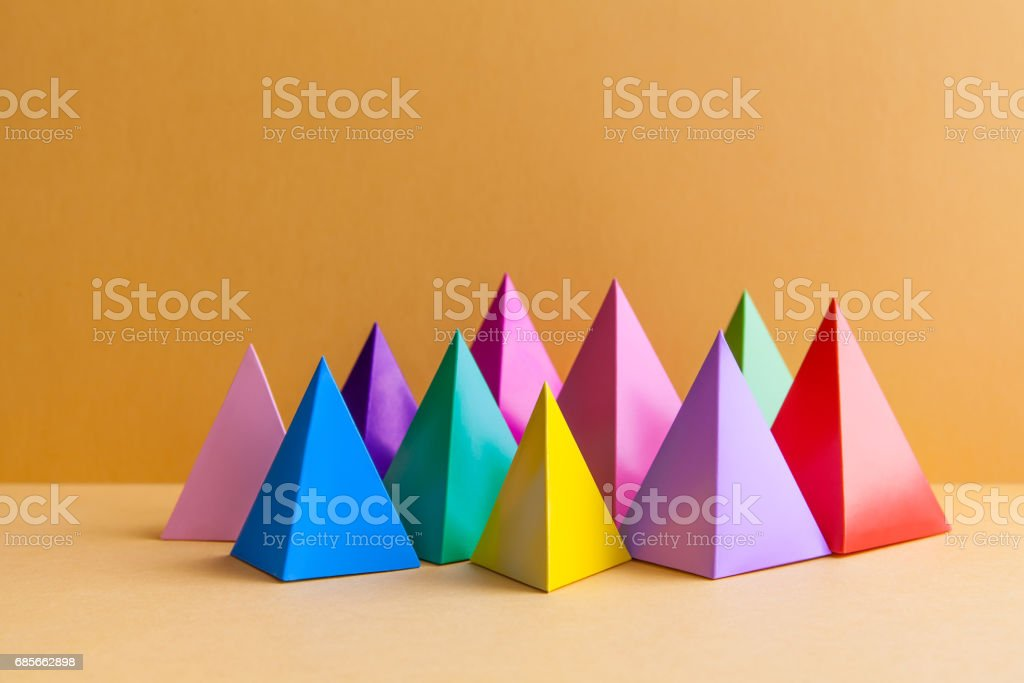 Colorful abstract geometric figures still life. Three-dimensional pyramid prism rectangular cube on orange background. Yellow blue pink green violet red colored objects stock photo