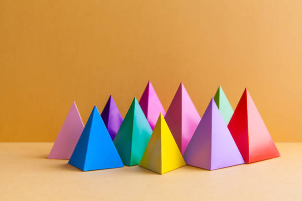 colorful abstract geometric figures still life. three-dimensional pyramid prism rectangular cube on orange background. yellow blue pink green violet red colored objects - geometria - fotografias e filmes do acervo