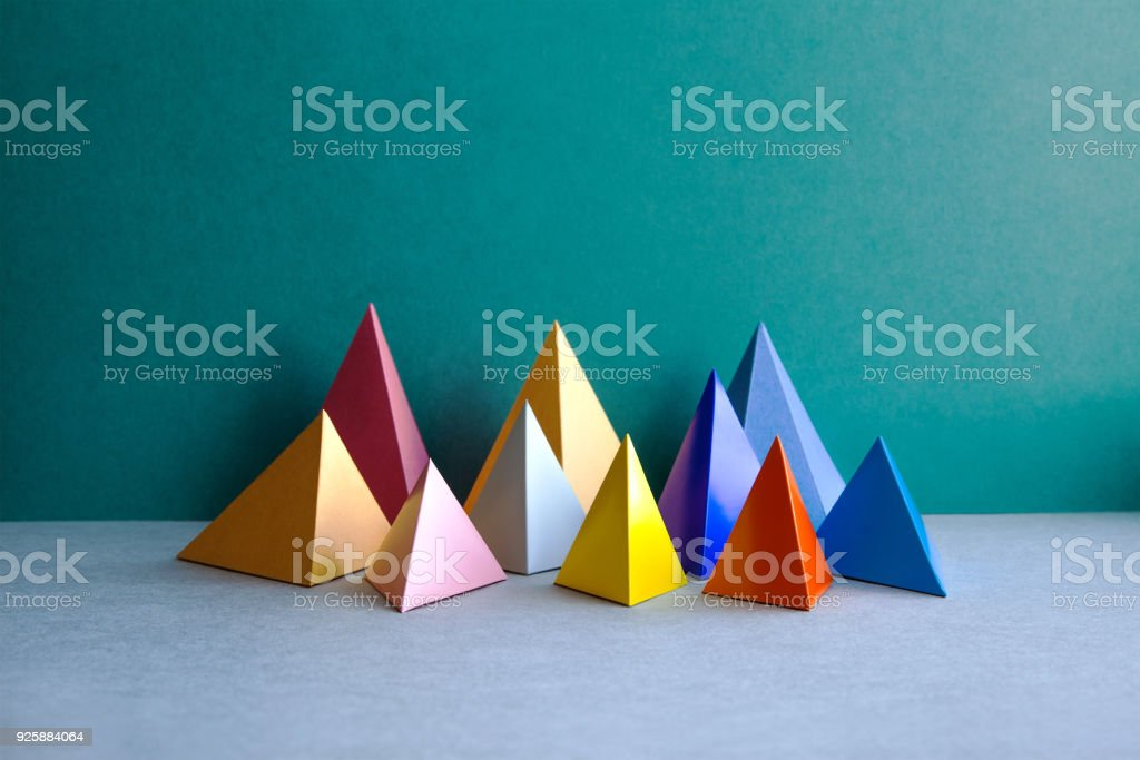 Colorful abstract geometric figures. Three-dimensional pyramid rectangular objects on green gray background. Yellow blue pink violet red colored tetrahedron Platonic solids background stock photo