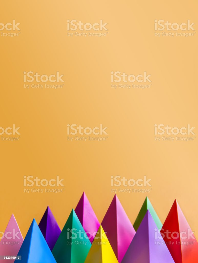 Colorful abstract geometric figures. Three-dimensional pyramid prism shapes, orange background. Yellow blue pink green violet red colored objects, textured paper surface. Copy space, vertical royaltyfri bildbanksbilder