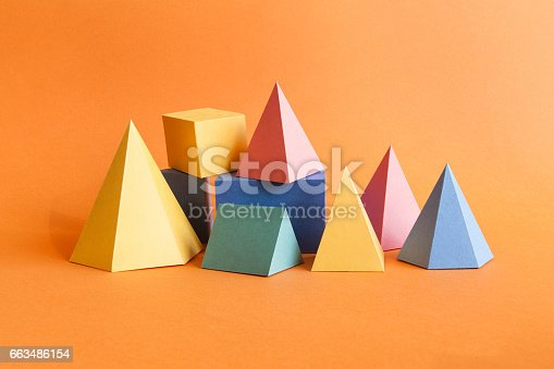 istock Colorful abstract geometrical composition. Three-dimensional prism pyramid rectangular cube objects on orange paper background. Yellow blue pink green colored solid figures, soft focus photo 663486154