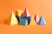 Colorful abstract geometrical composition. Three-dimensional prism pyramid rectangular cube objects on orange paper background. Yellow blue pink green colored solid figures, soft focus photo