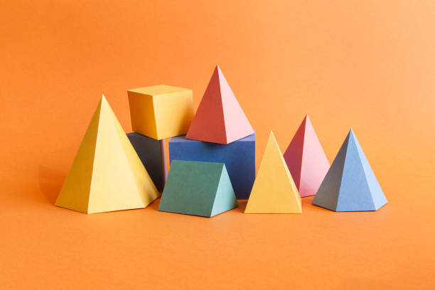 Colorful abstract geometrical composition. Three-dimensional prism pyramid rectangular cube objects on orange paper background. Yellow blue pink green colored solid figures, soft focus photo ストックフォト