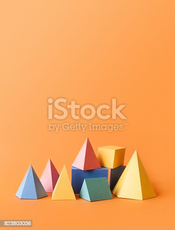 istock Colorful abstract geometrical composition. Three-dimensional prism pyramid rectangular cube objects on orange paper background. Yellow blue pink green colored solid figures, vertical copy space photo 823803036
