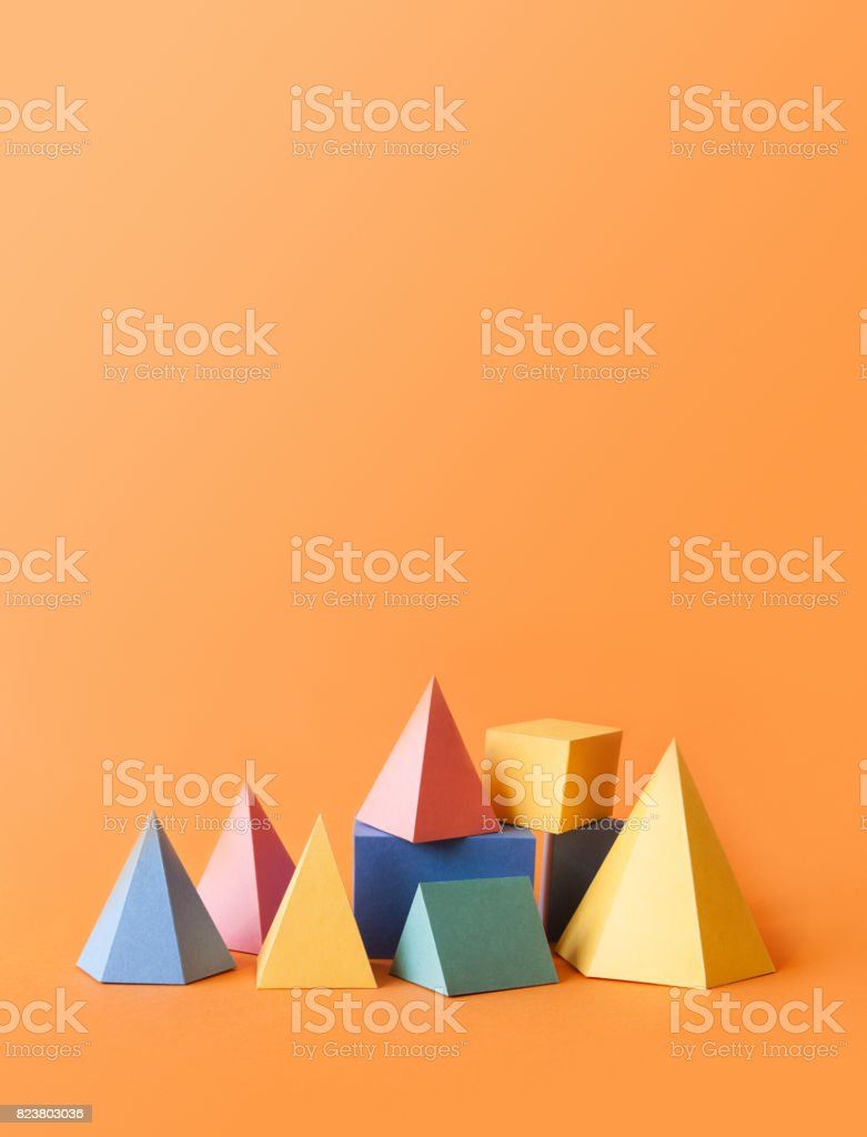 Colorful abstract geometrical composition. Three-dimensional prism pyramid rectangular cube objects on orange paper background. Yellow blue pink green colored solid figures, vertical copy space photo stock photo