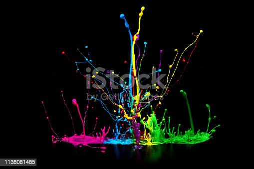 Colorful abstract paint splashing on audio speaker isolated on black background