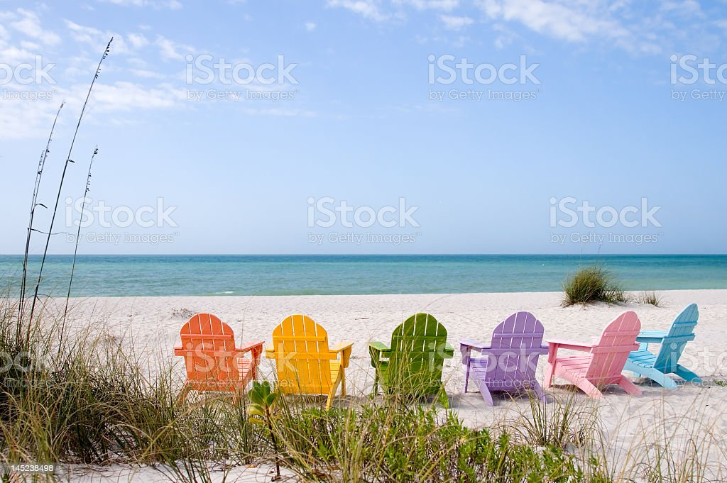 Colorful Adirondack chairs facing a white sandy beach stock photo