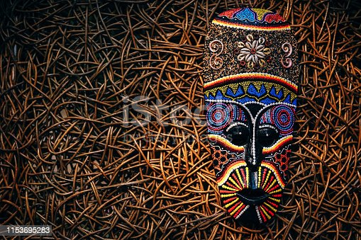 African style mask placed on a wooden background.