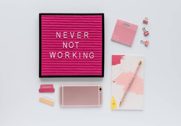 bunte agenda, büro-accessoires, handy und rosa brief board zitat auf weißem hintergrund - rosa zitate stock-fotos und bilder