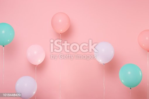 Colorful air balloons on pastel bright trending pink background. Decoration for birthday holiday party concept