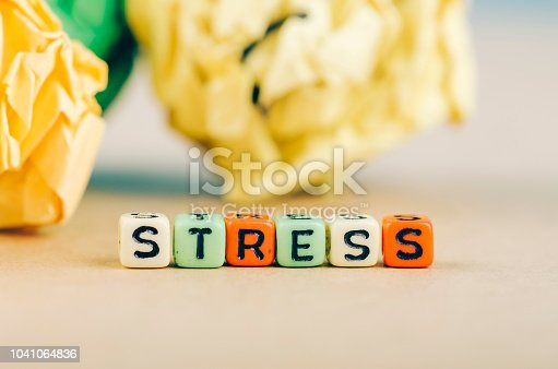 Colorful alphabet letter dice text on desk, spelling STRESS over crumple paper background