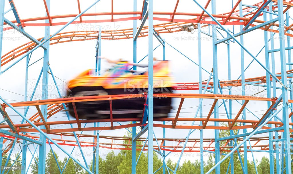 Colorful amusement park ride car going fast by with full speed. People having fun in theme park. Motion blur. stock photo
