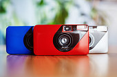 Colorful analog vintage 35mm film cameras in arrangement close to each other on a wooden table