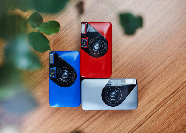 Colorful analog vintage 35mm film cameras lying in arrangement close to each other on a wooden table stock photo