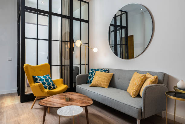 Colorful and cozy living room with a designer armchair and sofa along with a round decorative mirror and glass wall. Colorful and cozy living room with a designer armchair and sofa along with a round decorative mirror and glass wall. mirror stock pictures, royalty-free photos & images