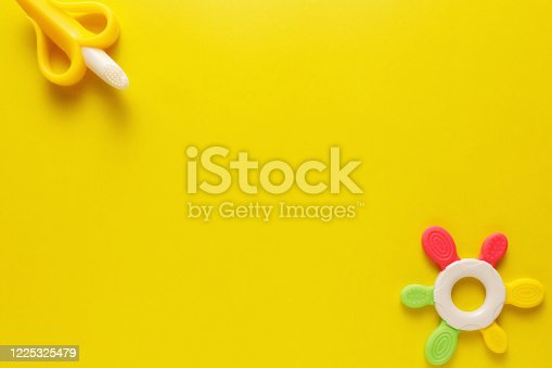 678159134 istock photo Colorful and various plastic toys for babies on a yellow background. Layout. Empty space for the text. Minimalism 1225325479