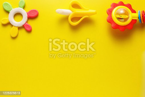 678159134 istock photo Colorful and various plastic toys for babies on a yellow background. Layout. Empty space for the text. Minimalism 1225325513