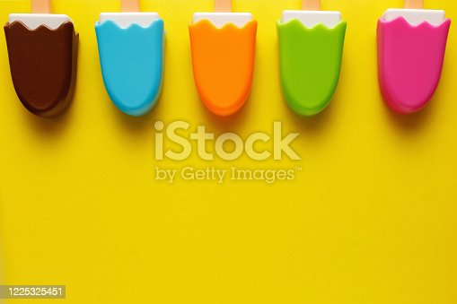 678159134 istock photo Colorful and various plastic toys ice cream with numbers for babies on a yellow background. Layout. Empty space for the text. Minimalism 1225325451