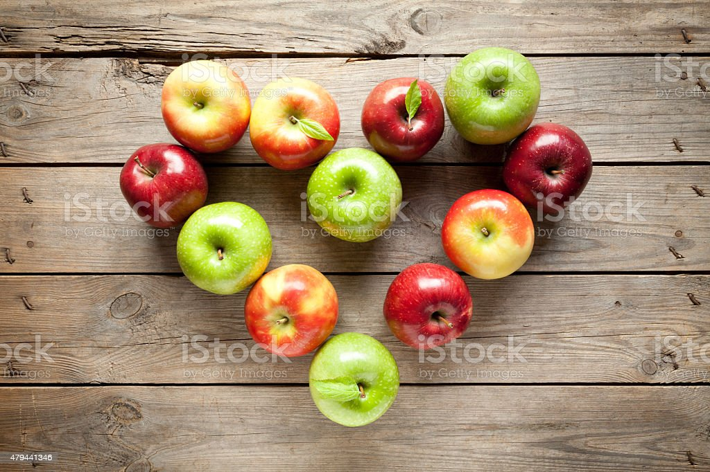 Colorful apple heart on old wooden table stock photo