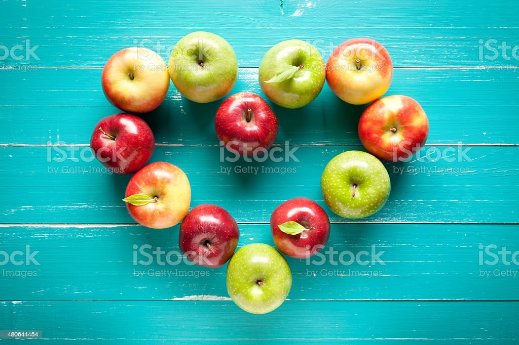 Colorful apple heart on turquoise wooden table stock photo