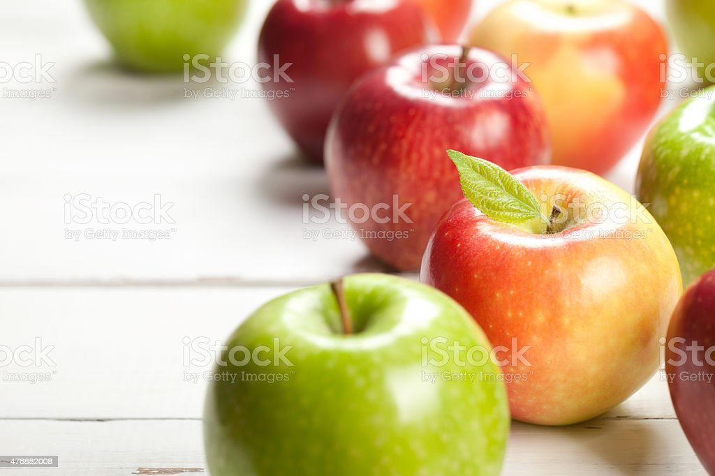 Colorful apples on white table stock photo