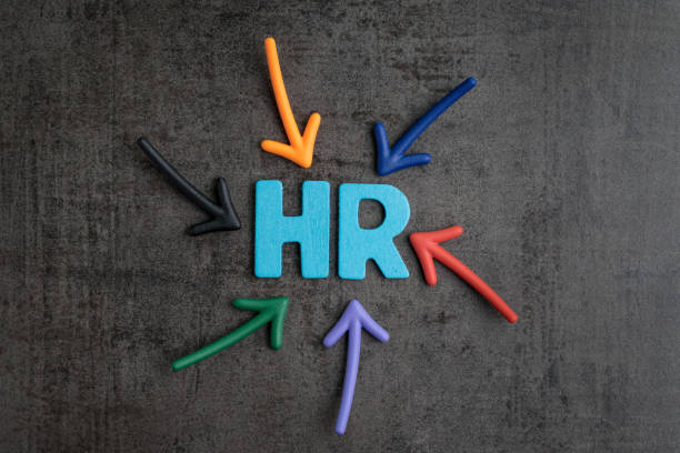 Colorful arrows pointing to the word HR at the center on black cement blackboard wall, represent Human Resource department, hiring new job or position in company stock photo
